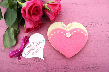 International Womens Day, March 8, heart shape cookies decorated as pink ladies dresses with bouquet of pink roses on vintage pink wood background, overhead. photo