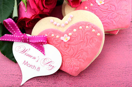 International Womens Day, March 8, heart shape cookies decorated as pink ladies dresses with bouquet of pink roses on vintage pink wood background, closeup with greeting card. photo