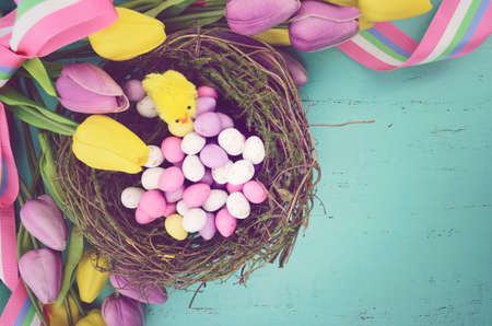 Retro vintage style filter Happy Easter background with painted Easter eggs in birds nest photo