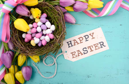 Happy Easter background with painted Easter eggs in birds nest, and yellow and purple silk tulips and ribbon on vintage style rustic distressed aqua blue wood table, with greeting tag.