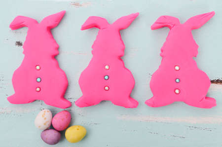 confectionary: Happy Easter pink confectionary sugar fondant cookie bunnies on pale aqua blue shabby chic vintage style wood table.