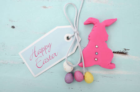 Happy Easter pink confectionary sugar fondant cookie bunny with greeting tag on pale aqua blue shabby chic vintage style wood table. photo