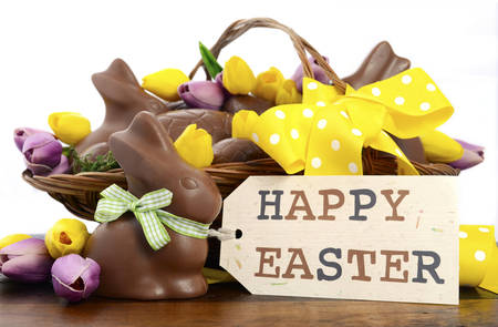 Happy Easter chocolate hamper of eggs and bunny rabbits in large basket with yellow and pink purple silk tulip flowers on dark wood table, with gift tag.
