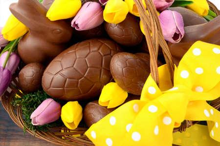 sol radiante: Feliz Pascua de chocolate cesta de huevos y conejitos en gran cesta con flores de tulipán de seda púrpura amarillo y rosa en la mesa de madera oscura, gastos generales.