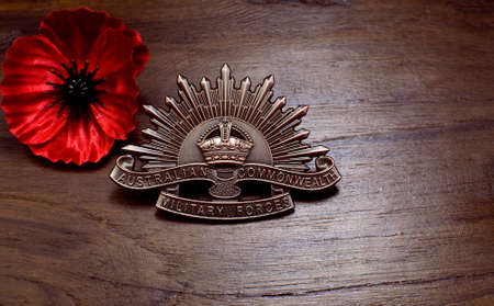ww2: ADELAIDE, AUSTRALIA - APRIL 2, 2014: Australian Anzac WWI rising star hat badge with red poppy on vintage wood background for Anzac Day and 100th anniversary centenary of the Gallipoli Campaign in 1915.