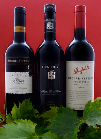 shiraz: ADELAIDE, SOUTH AUSTRALIA – FEBRUARY 23, 2015: Selection of three bottles of premium export quality Australian wine, including Henschke Tappa Pass Shiraz, Penfolds Cellar Reserve Sangiovese and Jacobs Creek Reserve Shiraz vintage 1998, produced in the B