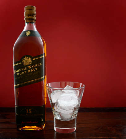 scotch whisky: ADELAIDE, SOUTH AUSTRALIA – FEBRUARY 23, 2015: Photo of a bottle of Johnnie Walker Green Label Pure Malt Scotch Whisky with ice in glass on a dark wood table against a red background, now discontinued and considered rare.