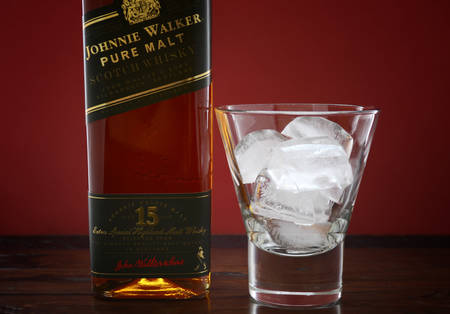 discontinued: ADELAIDE, SOUTH AUSTRALIA – FEBRUARY 23, 2015: Photo of a bottle of Johnnie Walker Green Label Pure Malt Scotch Whisky with ice in glass on a dark wood table against a red background, now discontinued and considered rare.