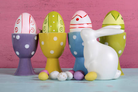 egg cups: Happy Easter eggs in polka dot egg cups with white ceramic bunny rabbit on pink and blue wood . Stock Photo