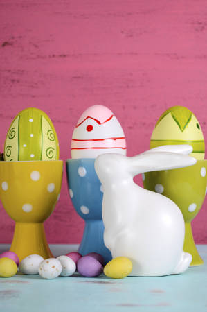 egg cups: Happy Easter eggs in polka dot egg cups with white ceramic bunny rabbit on pink and blue wood , vertical with copy space. Stock Photo