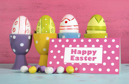 egg cups: Happy Easter eggs in polka dot egg cups on pink and blue wood , with greeting card.