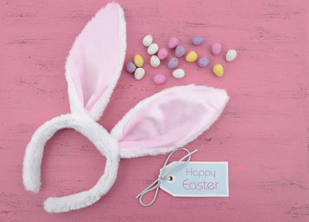 bunny ears: Happy Easter bunny ears with Easter eggs on pink wood .
