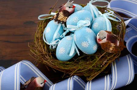 nido de pajaros: Feliz Pascua azul Decoraci�n de los huevos en las aves anidan en fondo de la tabla de madera oscura.