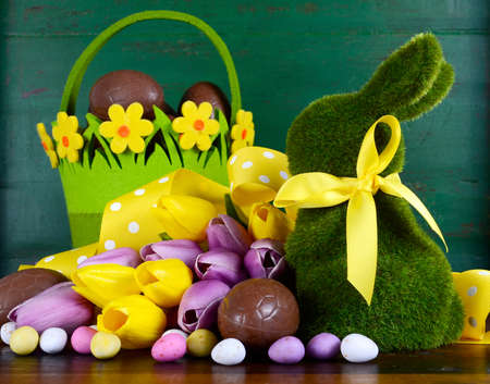 hamper: Happy Easter green moss grass bunny rabbit with basket of chocolate eggs and spring tulips against a green wood background.