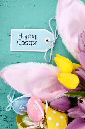 bunny ears: Feliz Pascua orejas de conejo en rosa aqua mesa de madera azul.