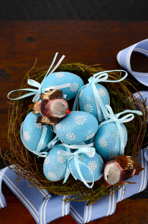 birds nest: Happy Easter blue decoration eggs in birds nest on dark wood table background. Stock Photo