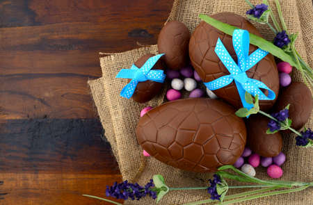 chocolate sweet: Happy Easter chocolate Easter eggs on dark wood country style table background.