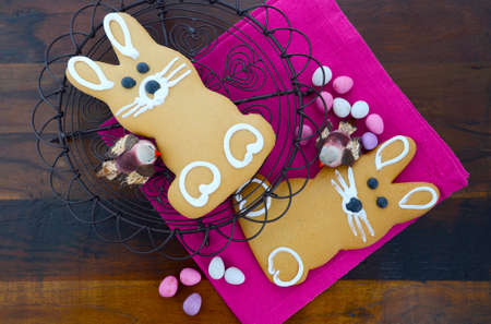 Easter gingerbread bunny cookie on vintage baking rack on dark wood table. photo