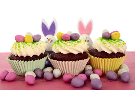 good food: Happy Easter cupcakes with bunny easter eggs on pink wood table. Stock Photo