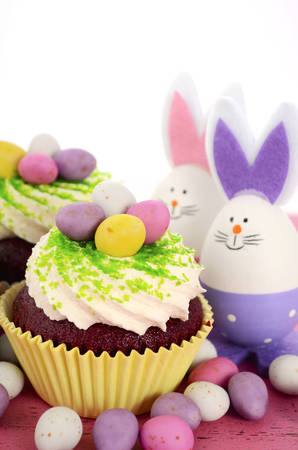 Happy Easter cupcakes with bunny easter eggs on pink wood table. photo