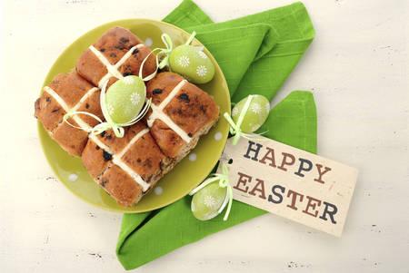 easter cross: Easter Fruit Hot Cross Buns on green polka dot plate on white wood table.