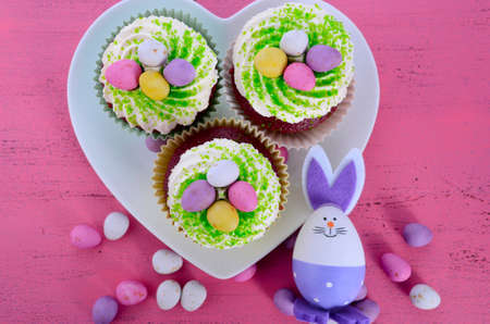 Happy Easter cupcakes on heart shape plate with bunny easter eggs on pink wood table. photo