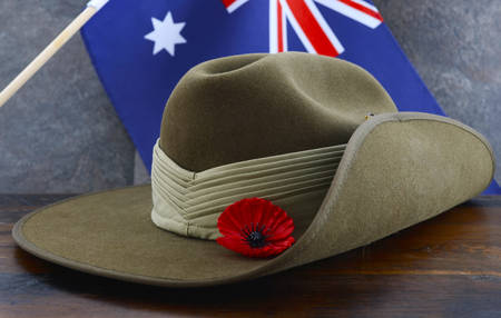 Anzac army slouch hat with Australian Flag on vintage wood background.