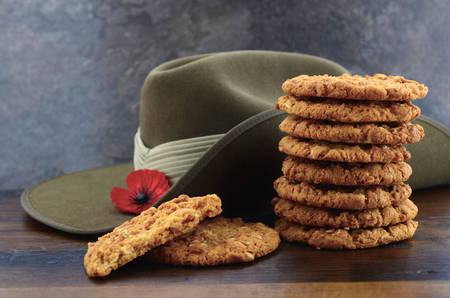 anzac: Australian Anzac biscuits with soldier slouch hat on dark vintage background.