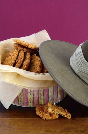 Australian Anzac biscuits in vintage biscuit tin with army soldier slouch hat. photo