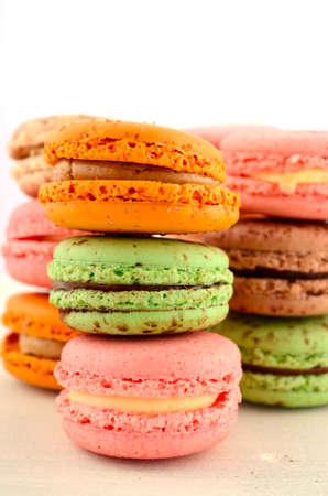 chocolate mint: Colorful strawberry, caramel and chocolate mint macaroons on white wood table.