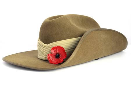 Anzac 日陸軍前かがみ帽子白い背景の赤いケシを持つ。