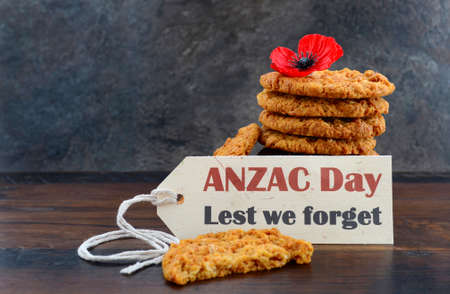 anzac: Australian Anzac biscuits with Anzac DAy, Lest We Forget message on dark wood and slate background.