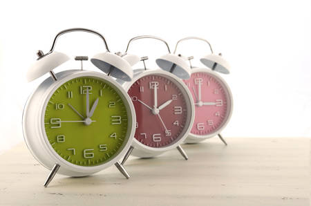Daylight Saving Time concept with three colorful retro style alarm clocks on white wood background. Stock Photo