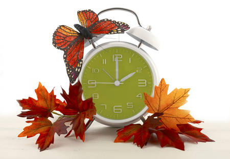 Daylight Saving Time Ends concept with Autumn Fall theme retro style alarm clock on white wood background.