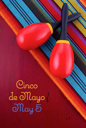 mayo: Happy Cinco de Mayo concept with maracas on Mexican style fabric on red wood distressed table.
