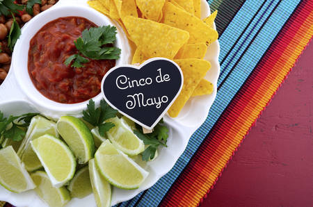 corn chips: Happy Cinco de Mayo party table with food platter including limes, corn chips, chilli beans and salsa on a red wood background.