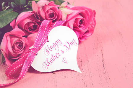 mothering: Happy Mothers Day gift of fresh pink roses on a pink distressed wood background with sample text, and applied retro vintage style filters.