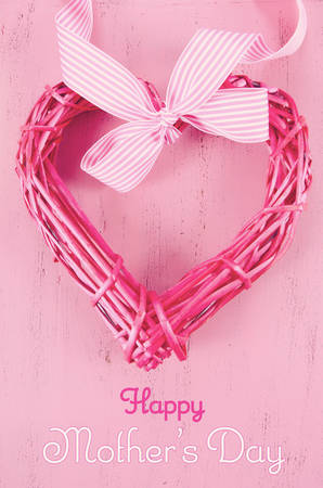 Happy Mothers Day gift of pink cane heart shape wreath with sample text, and applied retro vintage style filters. Stock Photo