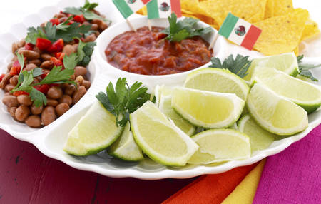 corn chips: Happy Cinco de Mayo bright colorful party food with chilli beans, corn chips, salsa and limes platter on red wood distressed red table. Stock Photo