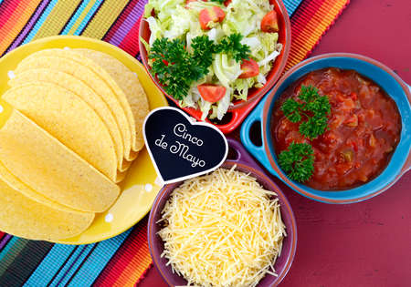 taco: Happy Cinco de Mayo bright colorful party with ingredients for assembling tacos on festive red wood table.