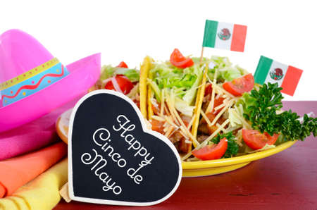 party with food: Happy Cinco de Mayo bright colorful party food with platter of tacos on red wood table.