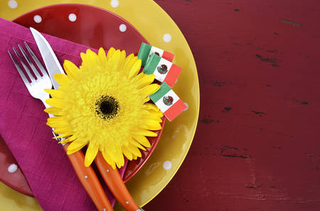 mayo: Happy Cinco de Mayo bright colorful party table place setting with bright gerbera daisy flowers on distressed red wood table. Stock Photo