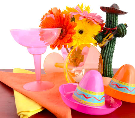 place setting: Happy Cinco de Mayo bright colorful party table place setting with bright gerbera daisy flowers on distressed red wood table. Stock Photo