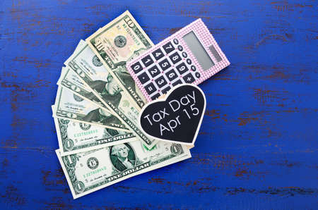 april 15: USA Tax Day, April 15, or money, savings and finance concept with USA dollar notes, calculator and Tax Day reminder on dark blue distressed wood table. Stock Photo