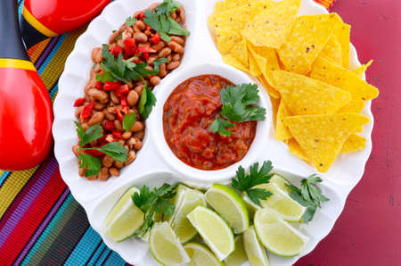 chips and salsa: Happy Cinco de Mayo bright colorful party food with chilli beans, corn chips, salsa and limes platter on red wood distressed red table. Stock Photo