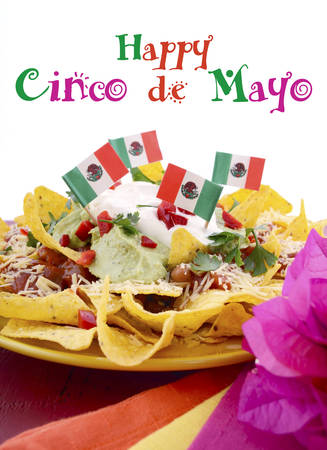 mexican flag: Happy Cinco de Mayo party table with nachos food platter and bright orange, red, and pink napkins on a red wood background.