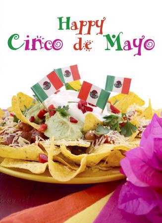 bandera mexicana: Mesa Feliz fiesta de Cinco de Mayo con plato de comida de nachos y naranja brillante, rojo, y las servilletas de color rosa sobre un fondo de madera roja.