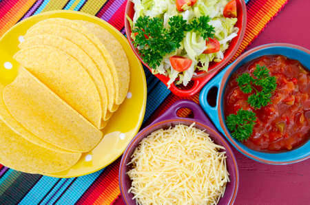 mayo: Happy Cinco de Mayo bright colorful party with ingredients for assembling tacos on festive red wood table.