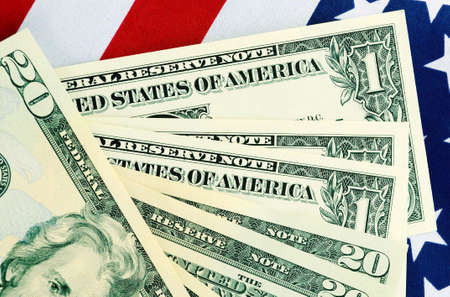 thrifty: USA Tax Day, April 15, or money, savings and finance concept with calculator and USA dollar notes on American flag, with serial numbers removed.