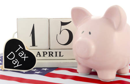 april 15: April 15 calendar for USA Tax Day with piggy bank on stars and stripes flag against a white background. Stock Photo